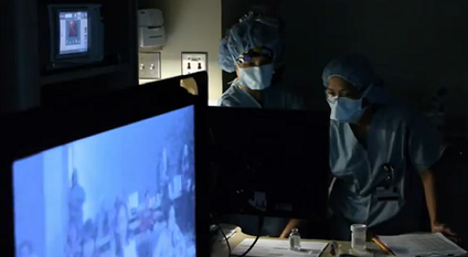 Northwestern Medicine Scholars seen on monitor watch from the classroom as the operating room (OR) team prepares for surgery.