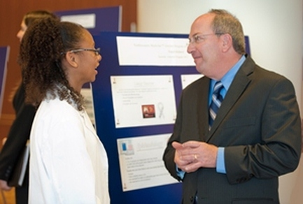 Kaya (Class of 2014) presents her research findings from the Northwestern Medicine Scholars 2011 Summer Intensive: Oncology 101 to Senior VP and advisory board member Dean Manheimer.